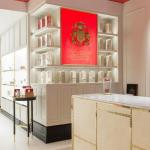 The company's coat of arms, set into a red lightbox, draws the eye through the store, Image Courtesy © Kate Berry