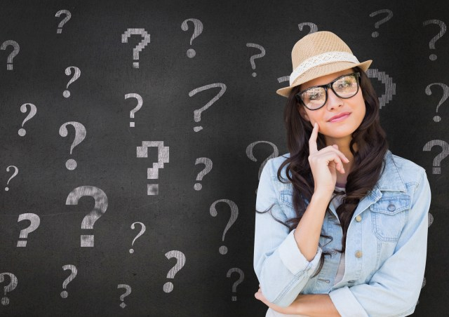 Digital composition of thoughtful woman in straw hat standing in front of chalkboard with question marks