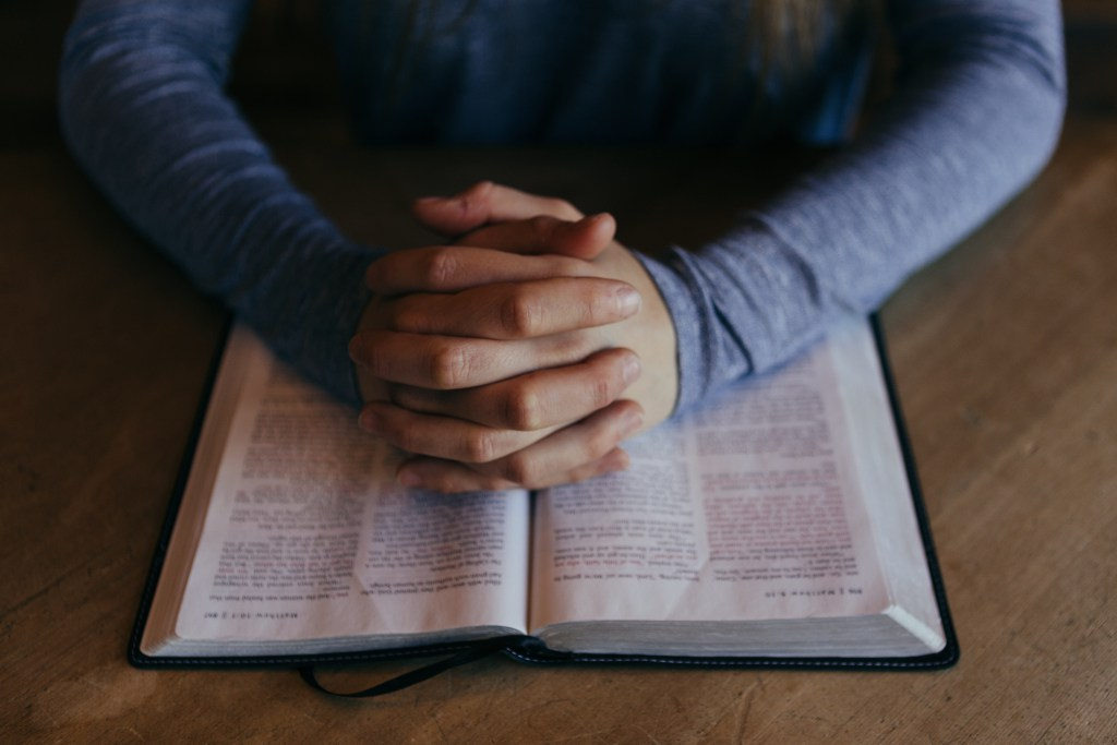 prayer-hands-folded-and-bible-unsplash