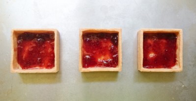 Place strawberry preserves on the bottoms of each tart.