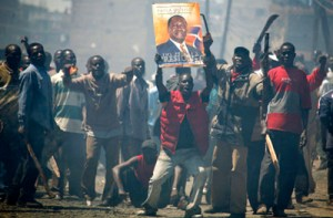 "Opposition supporters holding a poster of their leader Raila Odinga of Orange Democratic Movement (ODM) react during post election ethnic violence in Nairobi, January 2, 2008. President Mwai Kibaki's government accused rival Raila Odinga's party of unleashing ""genocide"" in Kenya on Wednesday as the death toll from tribal violence over a disputed election passed 300. REUTERS/Stringer (KENYA) KENYA OUT"
