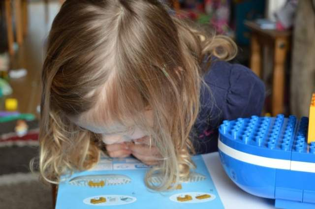 girl reading instructions to make toy boat