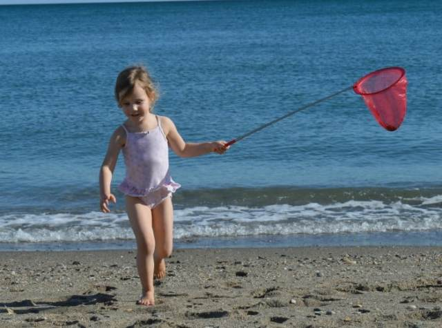 child playing with scrunch net on beach