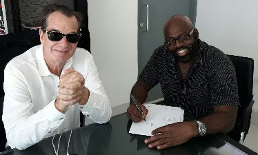 "Reggae Sumfest head honcho Josef ""Joe"" Bogdanovich (L) looks on, as singer Richie Stephens signs on the dotted line to confirm his group's appearance at Sumfest 2017."