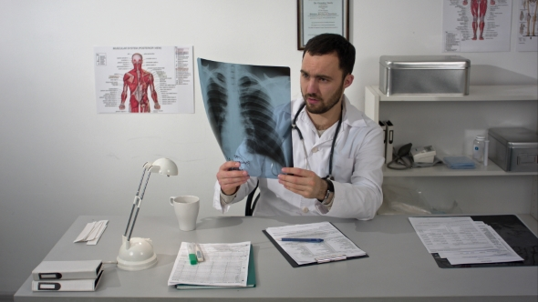 Serious Medical Doctor Sitting At Table And Looking Patients X-ray preview