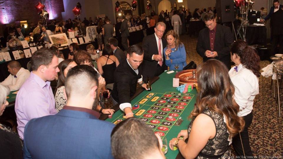 People standing around a roulette table.