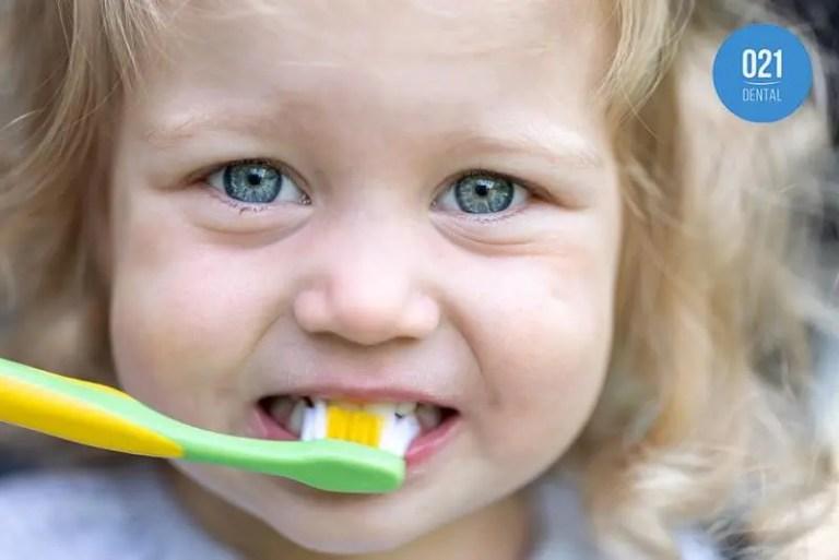 criança escovando seus dentes de leite