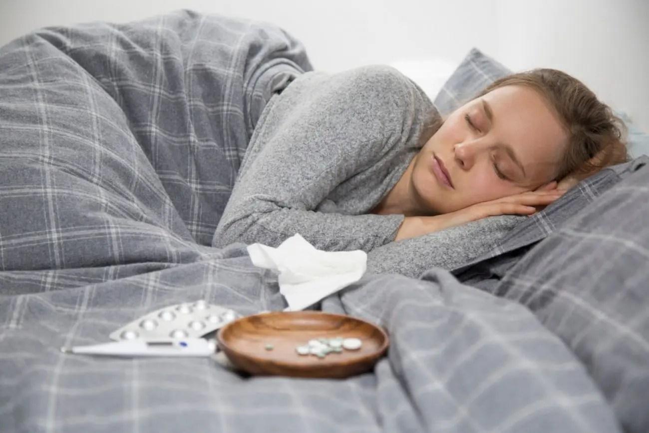 Mulher jovem dormindo com remédios e sintomas de bruxismo
