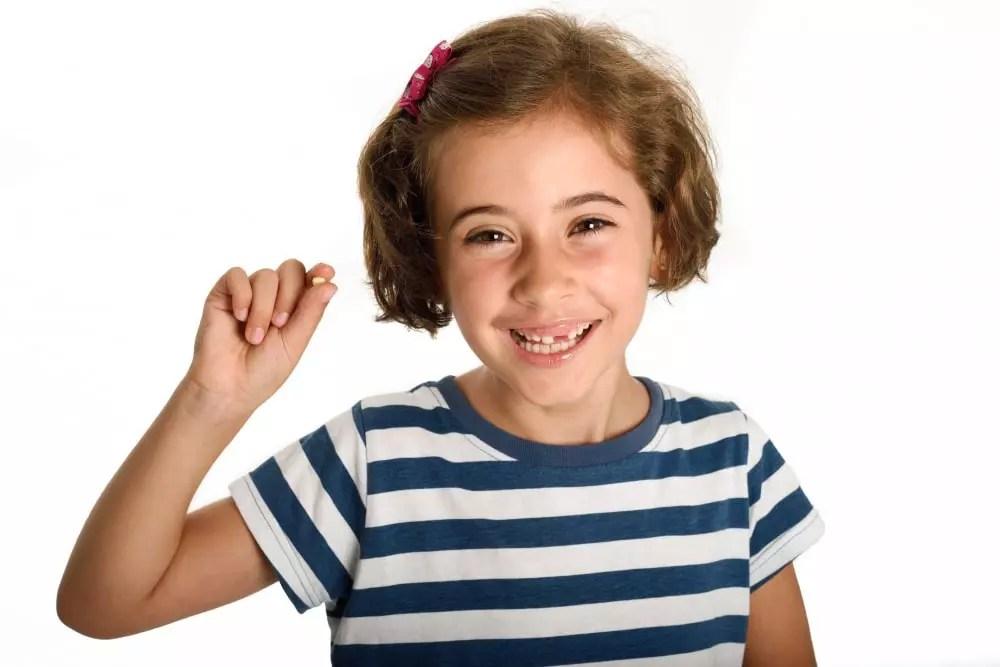 criança feliz mostrando seu dente de leite que caiu