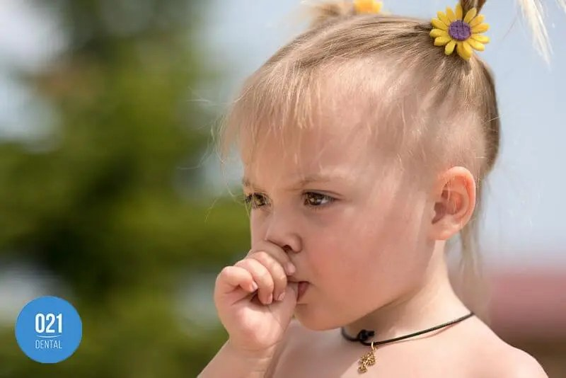 Menina chupando o dedo, uma das causas da mordida cruzada