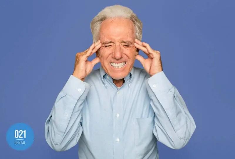 homem idoso com dor de cabeça causada pela mordida cruzada