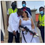 Couple Weds Holding Guns and Kissing (Photo)