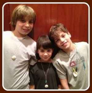 Max, Sam and Jack Eigen, wearing their necklaces.