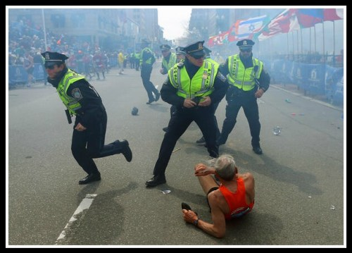 Police react immediately after today's explosion. This photo, taken by John Tlumacki, was tweeted by Boston Globe Sports. (From Business Insider)