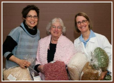 Ellen Lane (left) and Mary Heery (right) present Mary Ann Strolin with the first Knit One, Nibble One shawl at Norwalk Hospital's Smilow Breast Health Center.