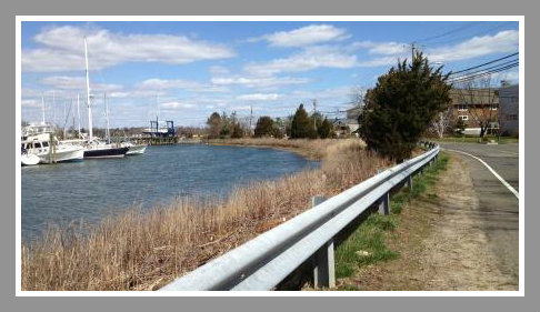 A guardrail separates  Harbor Road from the water.