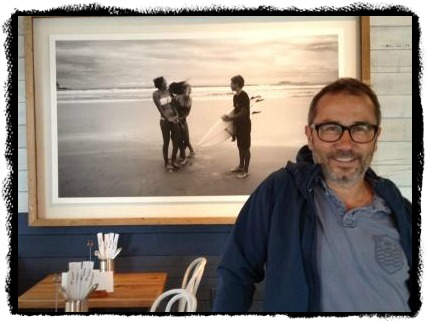 Owner Sasa Mahr-Batuz stands in front of one of his own photos: a dramatic beach scene.