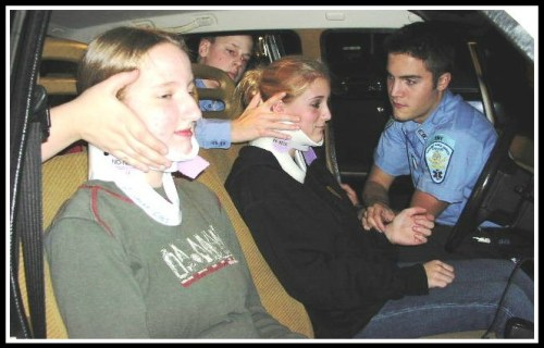 """Rebecca Kamins (left) acts as a """"patient"""" during EMS training."""