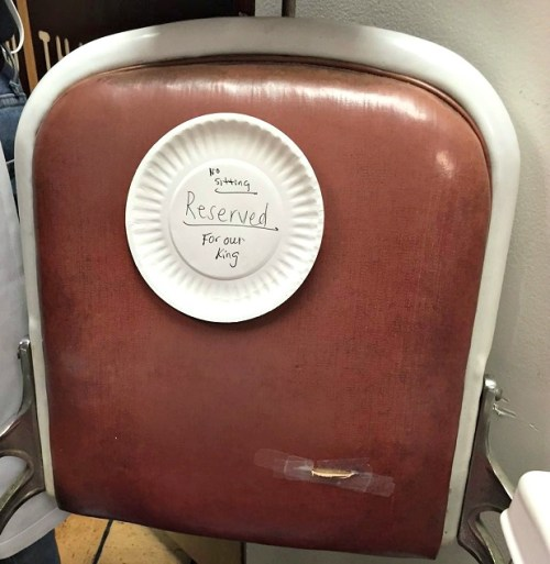 "A paper plate on the back of the barber chair where Lee regularly sits read, ""Reserved for the king."""