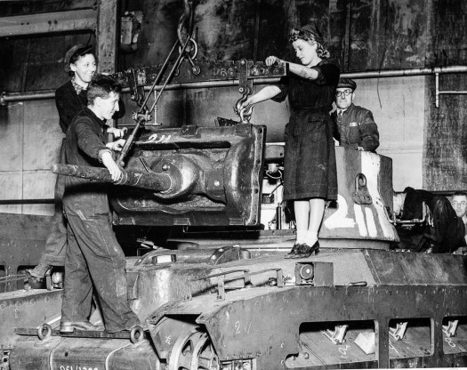 Workers installing turret on a tank