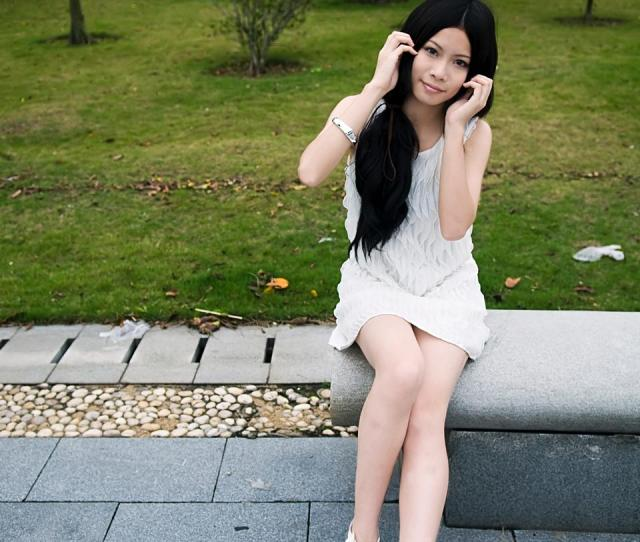Free Photos A Beautiful Chinese Girl Posing On A Bench Outdoors Peopleshot