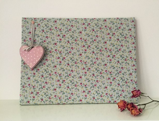 A photo of the finished cork board with a pink wooden heart attached for decoration
