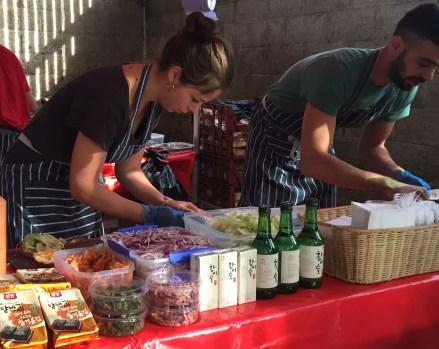 A photo of a lady and a man preparing food at GoGo Gogi Gui.
