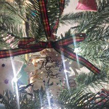 A photograph of the metal snowflake etched with Run Mummy Run. It's hanging on the Christmas tree.
