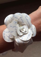 A photograph of a paper wrist corsage, decorated with words from the wedding reading, made by Julie for a wedding