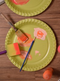 A photograph of two green paper plates being used to mix the paint shades