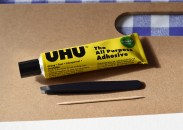 A photograph of the tube of UHU glue, tweezers and cocktail stick that Emma used