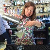A photograph of Emma pouring her shaken cocktail from the cocktail shaker, through a sieve into a martini-shaped glass