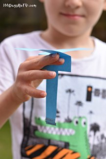 A photograph of Emma's eldest son holding the paper helicopter ready to fly.