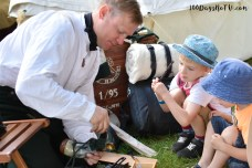 A photograph of Ollie and Ben being shown some soldier tools by a reenactor.