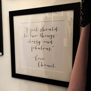 "A photograph of a framed quote by Coco Chanel saying, ""A girl should be two things: classy and fabulous"""