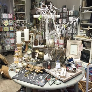 A photograph of the Eel Catcher's Daughter shop with a prominent table display covered in jewellery, candles and other little gifts