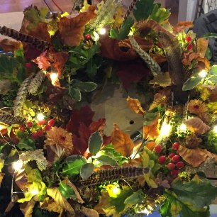 A photograph of a traditional-looking wreath with autumnal leaves, a few white fairy lights and even some game bird feathers