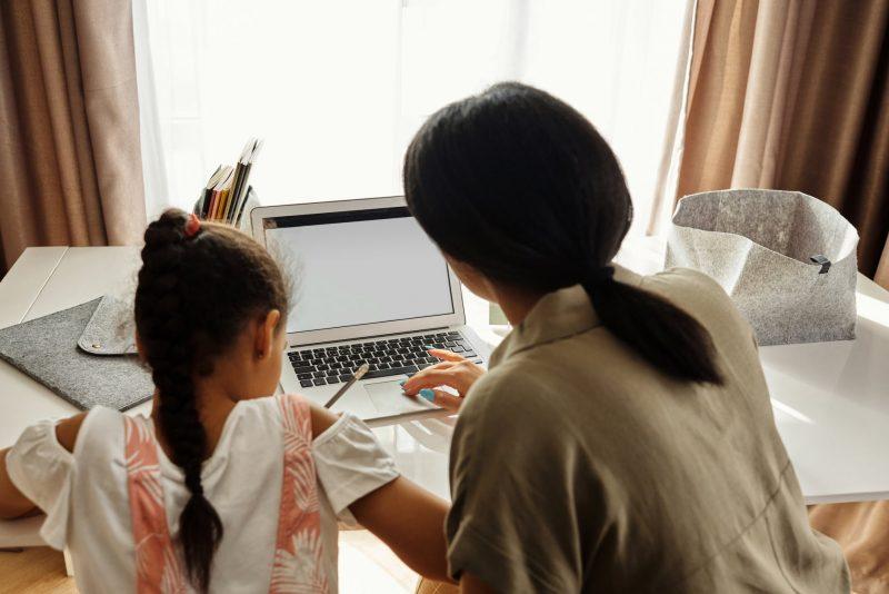 Mãe ensinando filha lição de casa