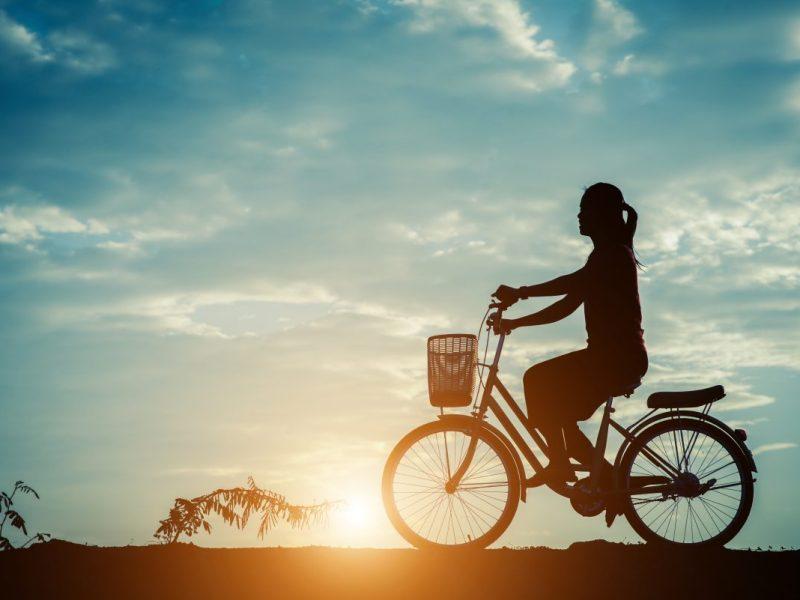 moça pedalando ao por do sol