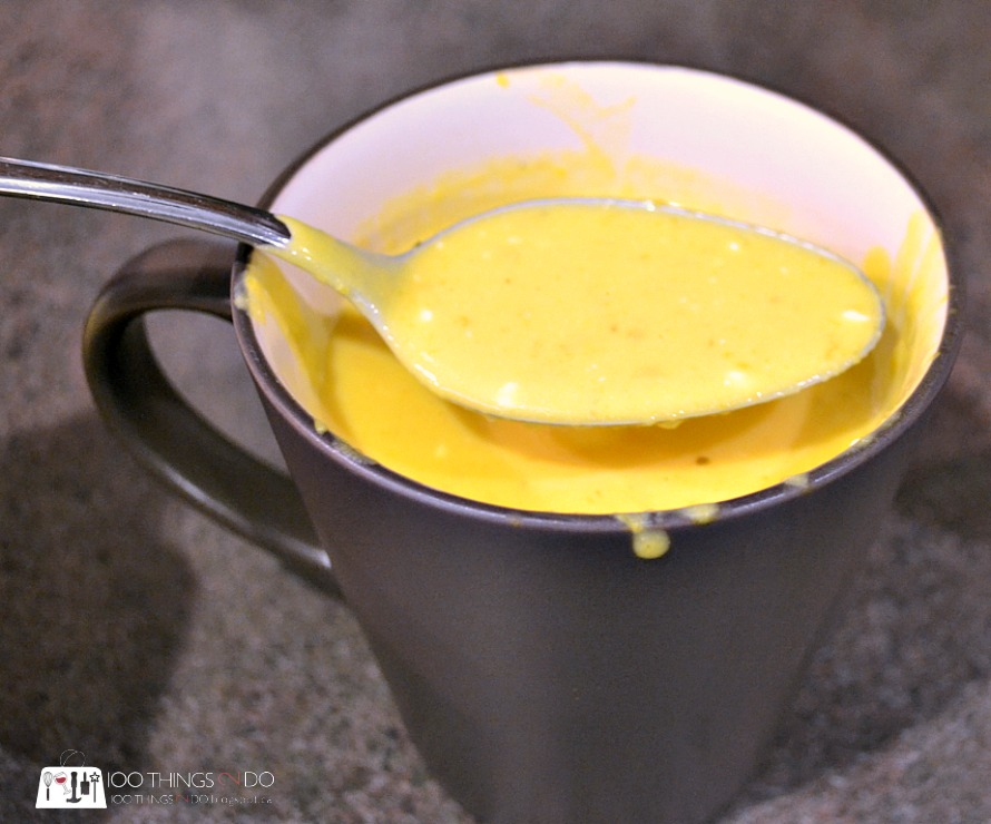 mug of soup with spoonful being raised out of it