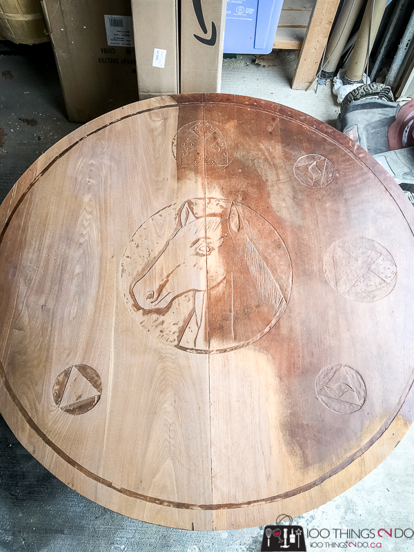 round coffee table with horse head carved into it