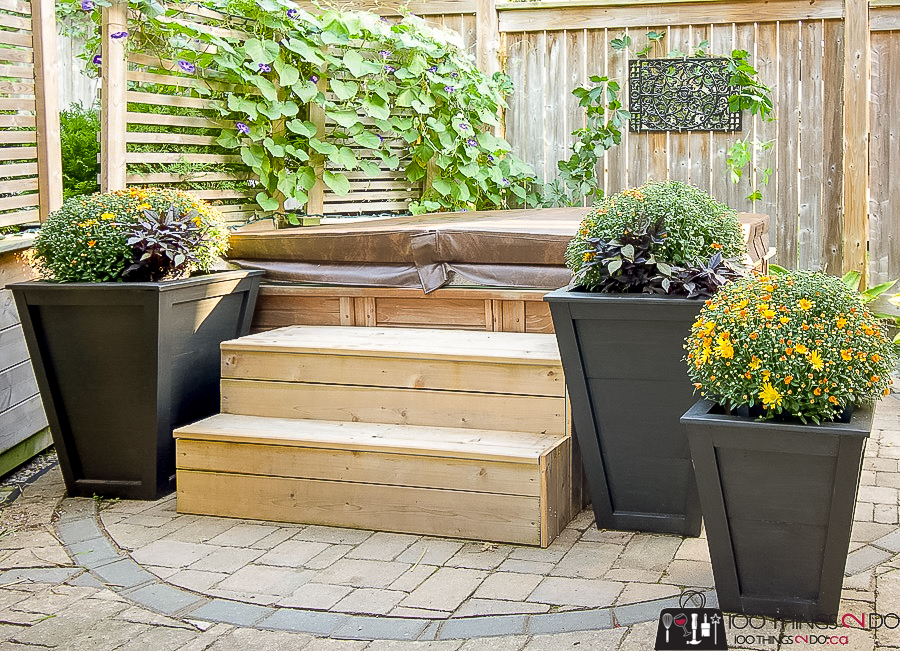 hot tub with stairs flanked by planters