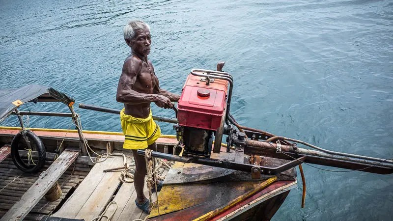 Old man maneuvering a longtail boat