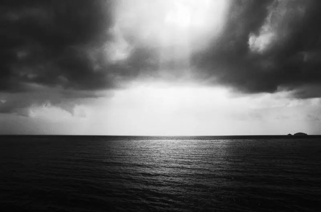 Sun shining through the clouds over the sea