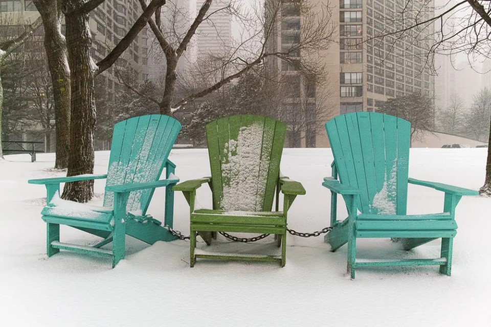 Green summer chairs in the snow