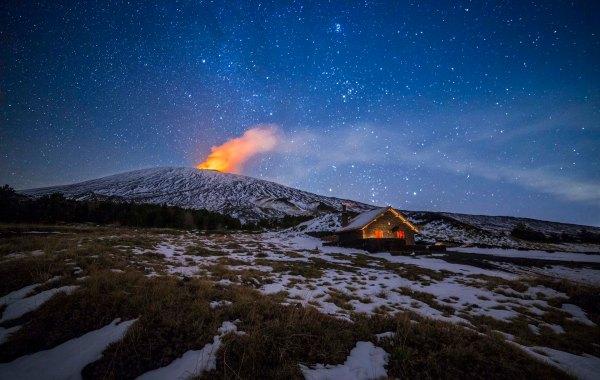 Rifugio Galvarina durante una notte di cielo stellato e un eruzione