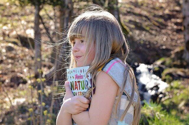 本を抱きしめ、微笑む少女