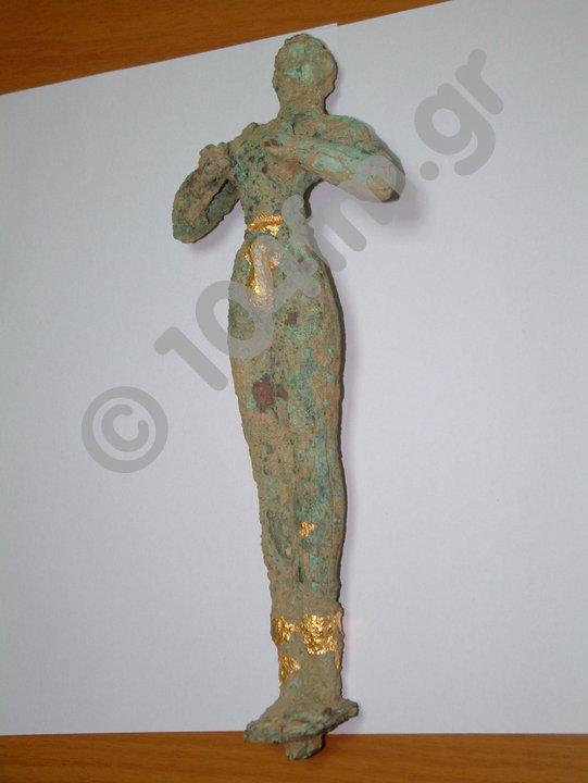 πρόκειται για χάλκινο ειδώλιο, Μεσομινωικής περιόδου (16ος – 15ος αιώνας π.Χ.), ύψους 30 cm, που απεικονίζει ένα Κούρο σε στάση λατρείας με τα χέρια διπλωμένα στο στήθος