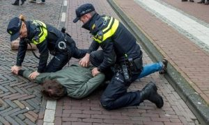 Twee agenten drukken verdachte tegen de grond