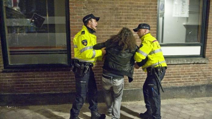 Twee agenten houden verdachte stevig vast